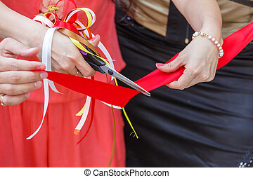 Grand opening. scissors cut the red ribbon. close-up