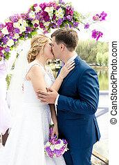 cerimonia, sposo, giovane, sposa, arco, sotto, baciare, matrimonio