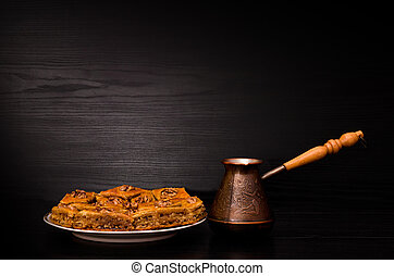Cezve of coffee and a plate of baklava with honey on a black background