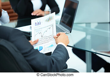 close-up of the Financial Director holds the schedule of the financial condition of the company in office at workplace