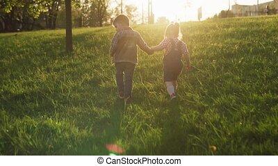 chłopiec, mały, pieszy razem, pole, zachód słońca, dzierżawa wręcza, dziewczyna, wzdłuż