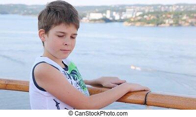 chłopiec, stoi, na, statek, pokład, przeciw, morze, i, miasto, w, popołudnie