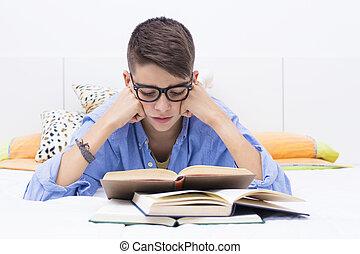chłopiec, teenage, książki, łóżko, badając