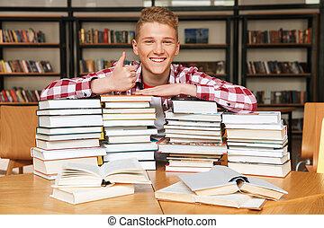 chłopiec, teenage, posiedzenie, biblioteka, stół, uśmiechanie się