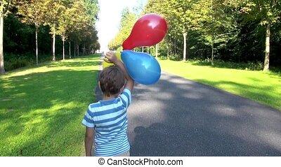 chłopiec, z, balony, w parku
