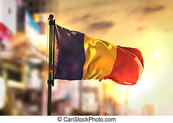 Chad Flag Against City Blurred Background At Sunrise Backlight