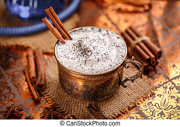 Chai latte spiced black tea beverage in antique mug with cinnamon