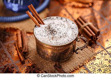 Chai latte spiced black tea beverage in antique mug with...