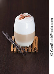 Chai Latte spiced tea beverage in glass mug with spices