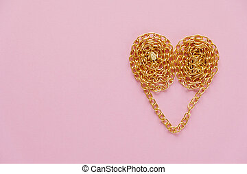 a gold chain laid out in the shape of a heart on a pink background