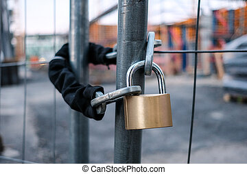 chain and padlock on gate at construction site - lock on...