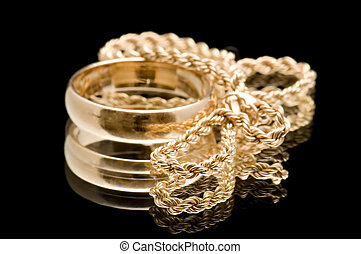 chain and ring on black - object on black - Gold ring on...