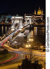 The Chain bridge Lanchid in Budapest Hungary, spanning the river danube featuring Saint Istvan Basilika at night