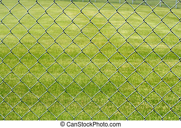 Chain Link Fence - A chain link fence in a field in a park...