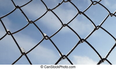 Chain link fence against sky in winter. Snow melting on...