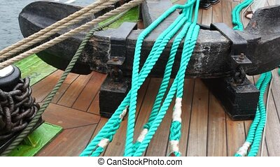 Chain of an anchor lies stranded on ship deck near rope
