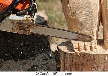 Chain saw cutting a piece of wood.