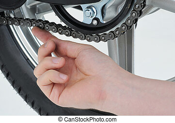 chain tension - motorcycle mechanic checking the tension on...