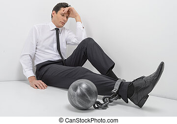 Chained businessman. Full length of depressed businessman sitting on the floor with shackles chained to his legs