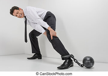 Chained businessman. Full length of hopeless businessman trying to go with shackles chained to his legs