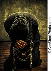Chained fanatic - Miserable monk praying on his knees in...
