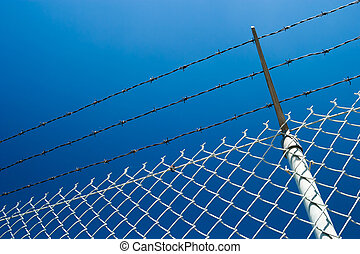 Chainlink fence and the blue sky - A chainlink fence with...