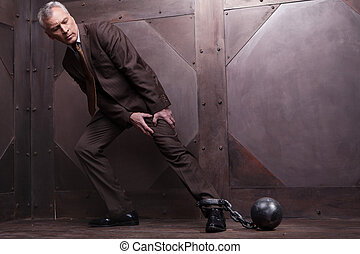 Chains on his leg. Full length of grey hair senior man in formalwear trying to go with the shackles on his leg