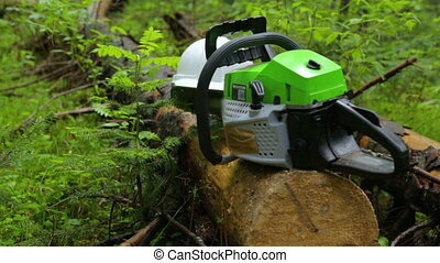 Chainsaw and helmet on log in forest
