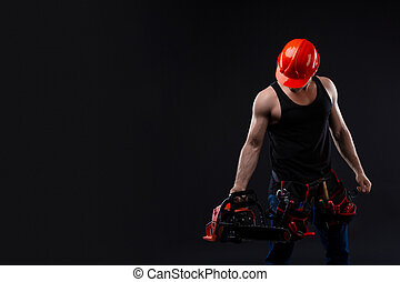 Chainsaw and young worker. The naked man broke the chainsaw. Attractive guy with tool on black background. Builder or lumberjack, wood processing