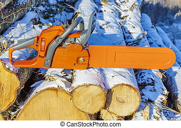 Chainsaw on pile of logs