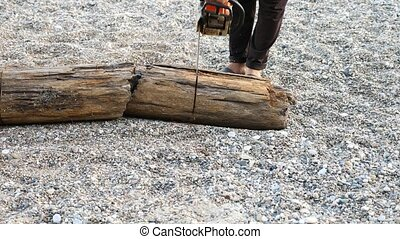 Chainsaw sawing wood. Man saws a log with a chainsaw, carried by the sea during a storm. Slow motion