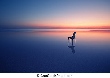 Chair among smooth water of lake at sunset