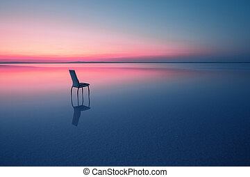 Chair among smooth water of lake at the sunset