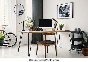 Chair at desk with computer desktop in home office interior with clock and poster. Real photo