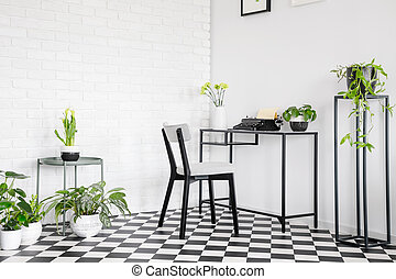 Chair at desk with typewriter in white and black workspace interior with plants. Real photo