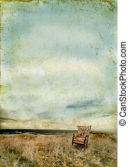 Upholstered chair in the grass by the sea. Grunge background with copy-space for your own text.