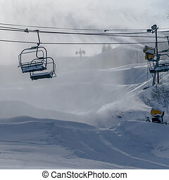 Chair lifts against artificial snow from snow guns. Frosty...