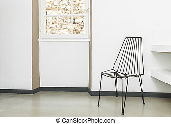 Chair made of wires in the empty room with white walls.