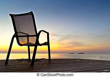 Chair on a pier near the sea during sunrise