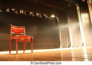 Red chair on empty stage lighted with spotlights