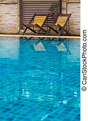 Chair on ground beside swimming pool