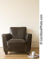 Chair with coffee mug and magazine beside it