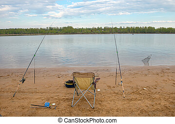 Chair with fishing equipment on the beach