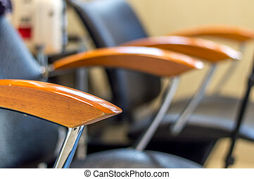 Chair with wooden armrests in beauty salon