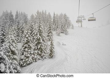 Chairlift in snowfall at alpine ski resort