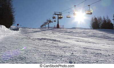 Chairlift lifts skiers up the mountain above an empty ski ...