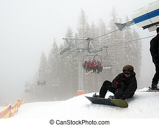 Chairlift with people in fog on ski slope. Snowboarder sitting at the lift wearing a ski mask and helmet.