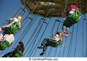 Chairoplane spinning with people against the blue sky
