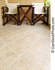 Chairs and table on tiled floor - Wooden chairs and table on...