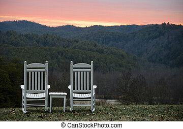 Chairs and Table Overlooking Hills at Sunset